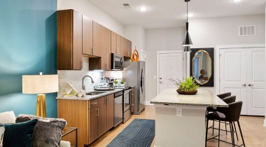 Apartment kitchen with large island, stainless steel appliances, and modern lighting at Cortland Cary