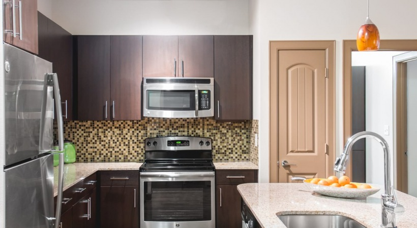Kitchen with stainless steel appliances at our luxury apartments near Legacy West