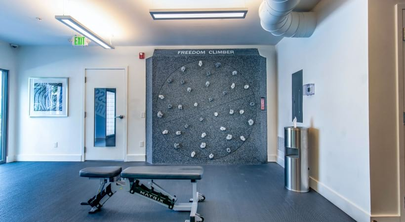 Gym with rock climbing wall at our modern apartments near Denver