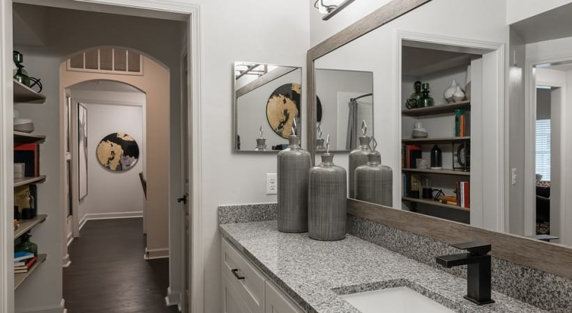 Bathroom with sleek granite countertops and modern lightings at our 1, 2, and 3 bedroom apartments for rent in Cypress, TX