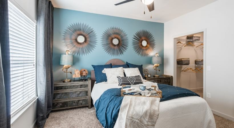 Bedroom with blue accent wall and cozy decor at our Cypress luxury apartments