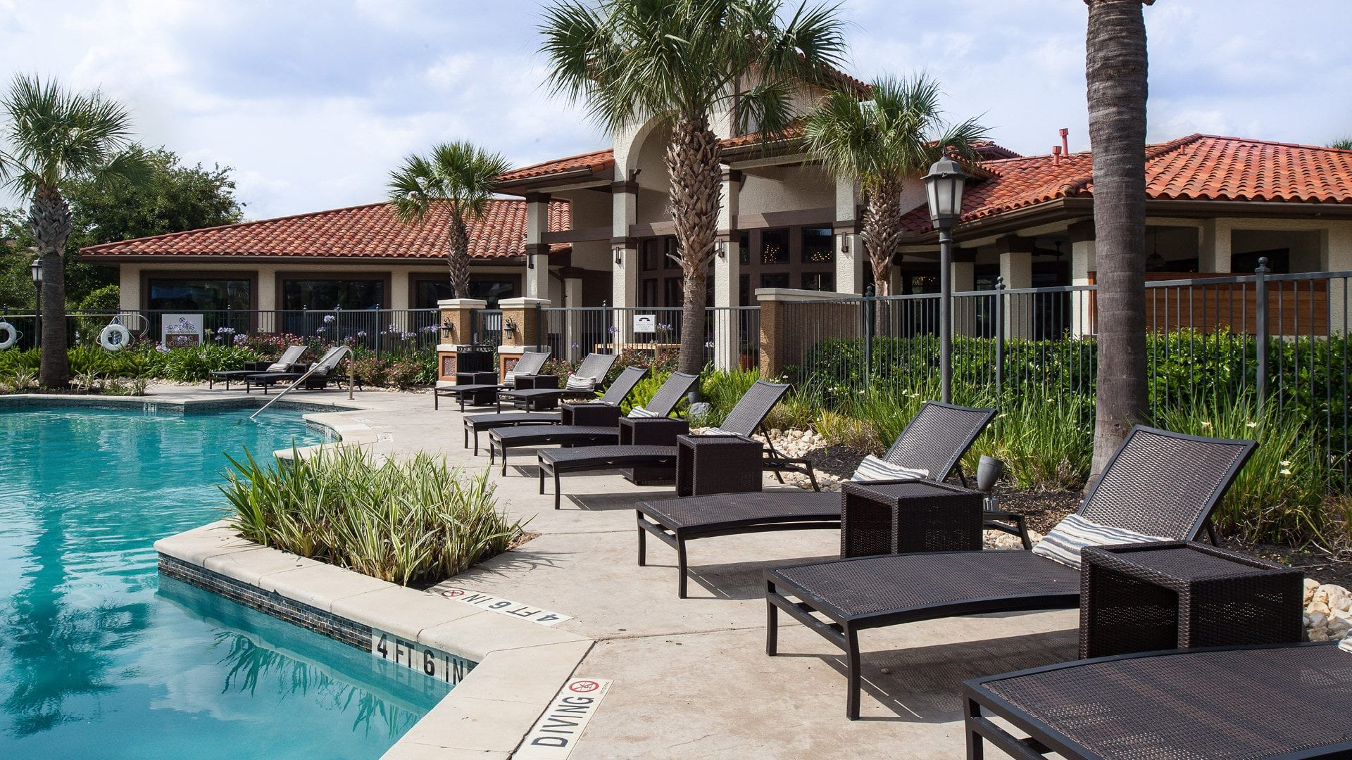 Lounge chairs by resort style pool at Cortland Coppery Springs