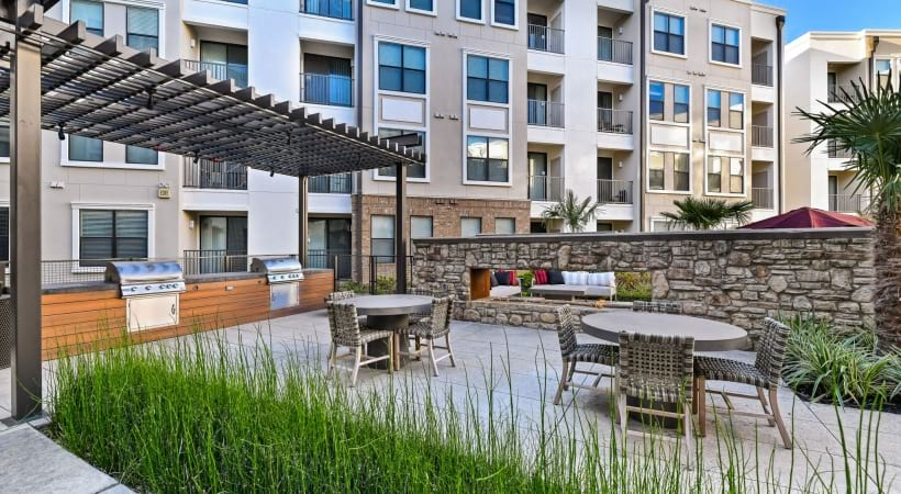 Outdoor kitchen with grilling station and firepit at our luxury apartments near Legacy West