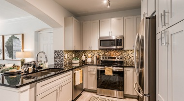 White-theme kitchen with black granite countertops at our modern apartment complexes in Houston, TX