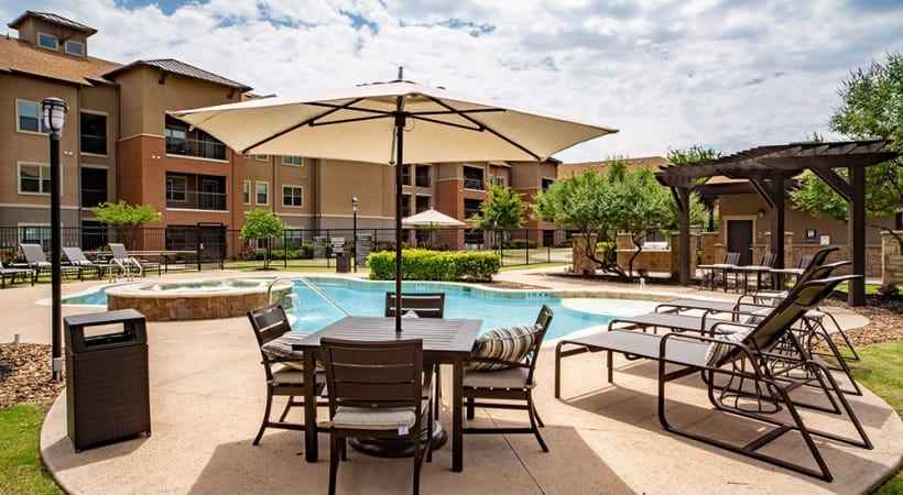 Resort style pool with lounge chairs at our over 55 apartments in Grand Prairie, TX