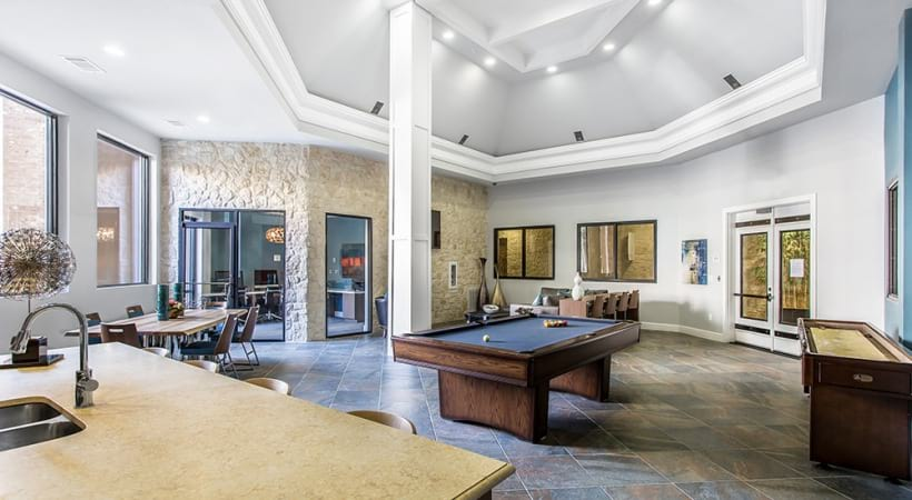 Our Frisco apartment clubhouse with pool table and seating areas