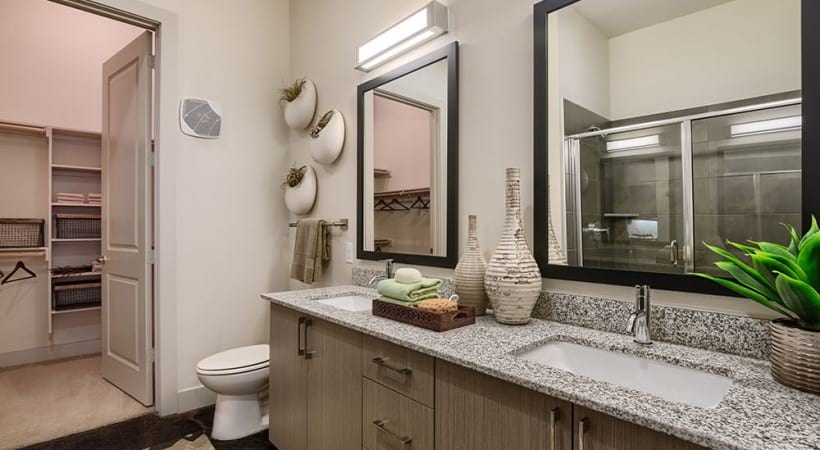 brightly lit bathroom with spacious walk-in closets
