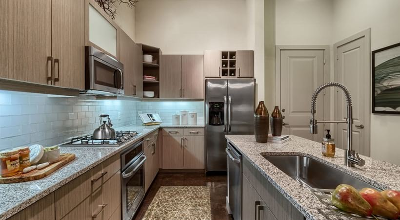 Kitchen with island and stainless steel appliances at Farmers Market apartments