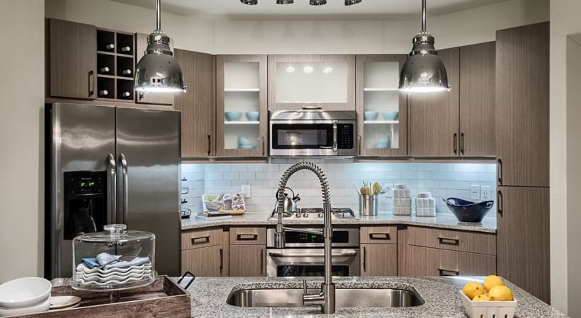 Modern kitchen with stainless steel appliances and modern lighting at our Downtown Dallas apartments for rent