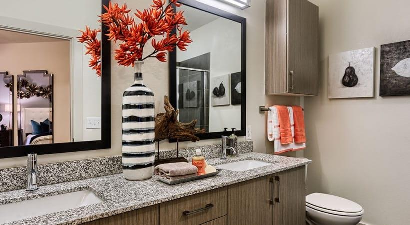 well lit bathroom with double sink vanities