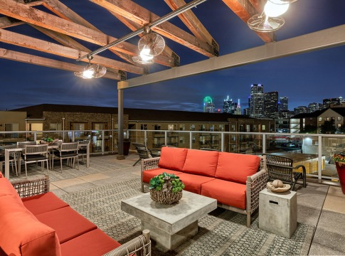brightly lit Rooftop Lounge with overhead fans overlooking dallas skyline
