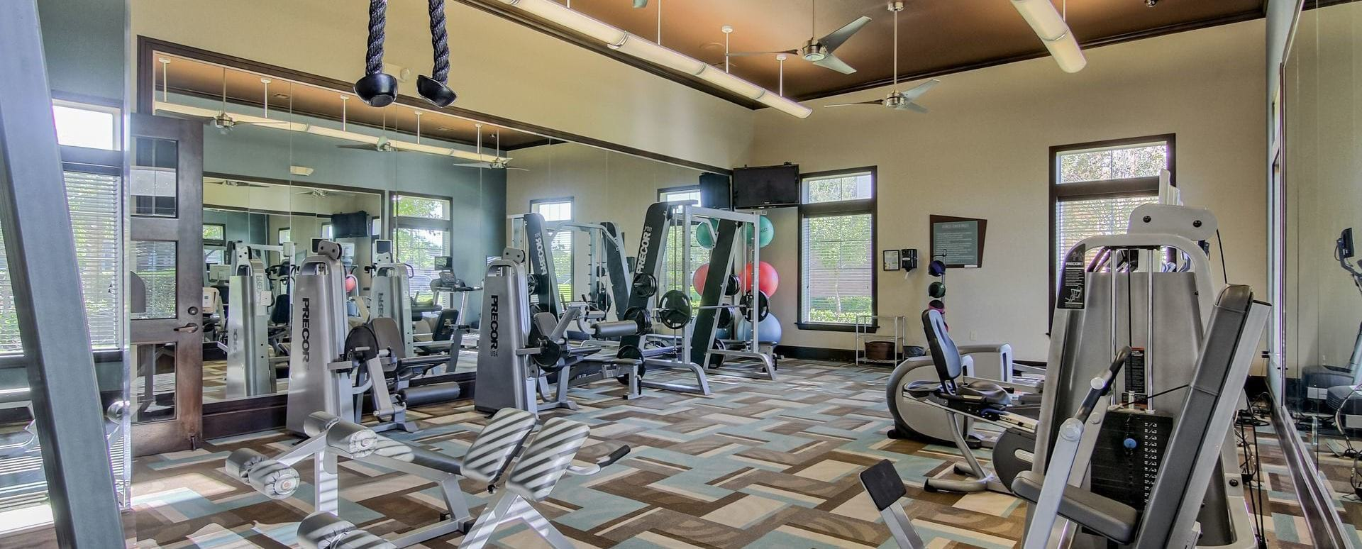 fitness center with ceiling fans and abundant lighting