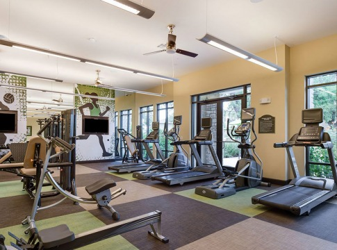 large, bright fitness center with tv monitors and cardio and strength training equipment