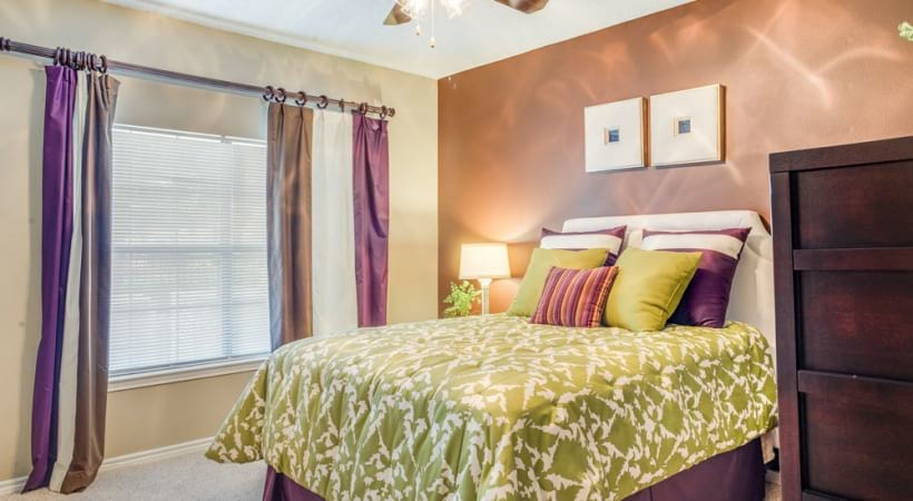 Large well lit bedroom with ceiling fan