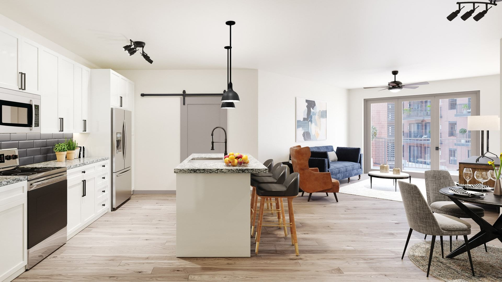 brightly lit kitchen and island open to living room and dining area