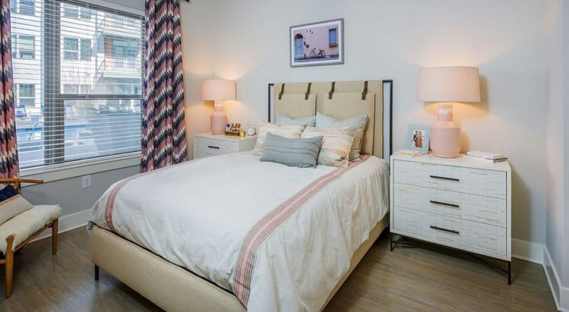 Bedroom with wood-style flooring and cozy decoration at our luxury apartments in Uptown Charlotte, NC