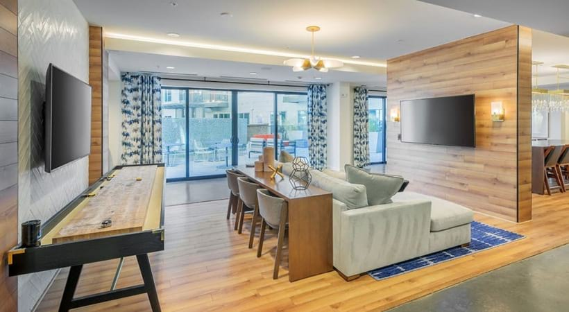 Party-ready residential lounge with HDTVs, kitchen, and comfortable seating at our upscale apartments in NoDa District, Charlotte NC
