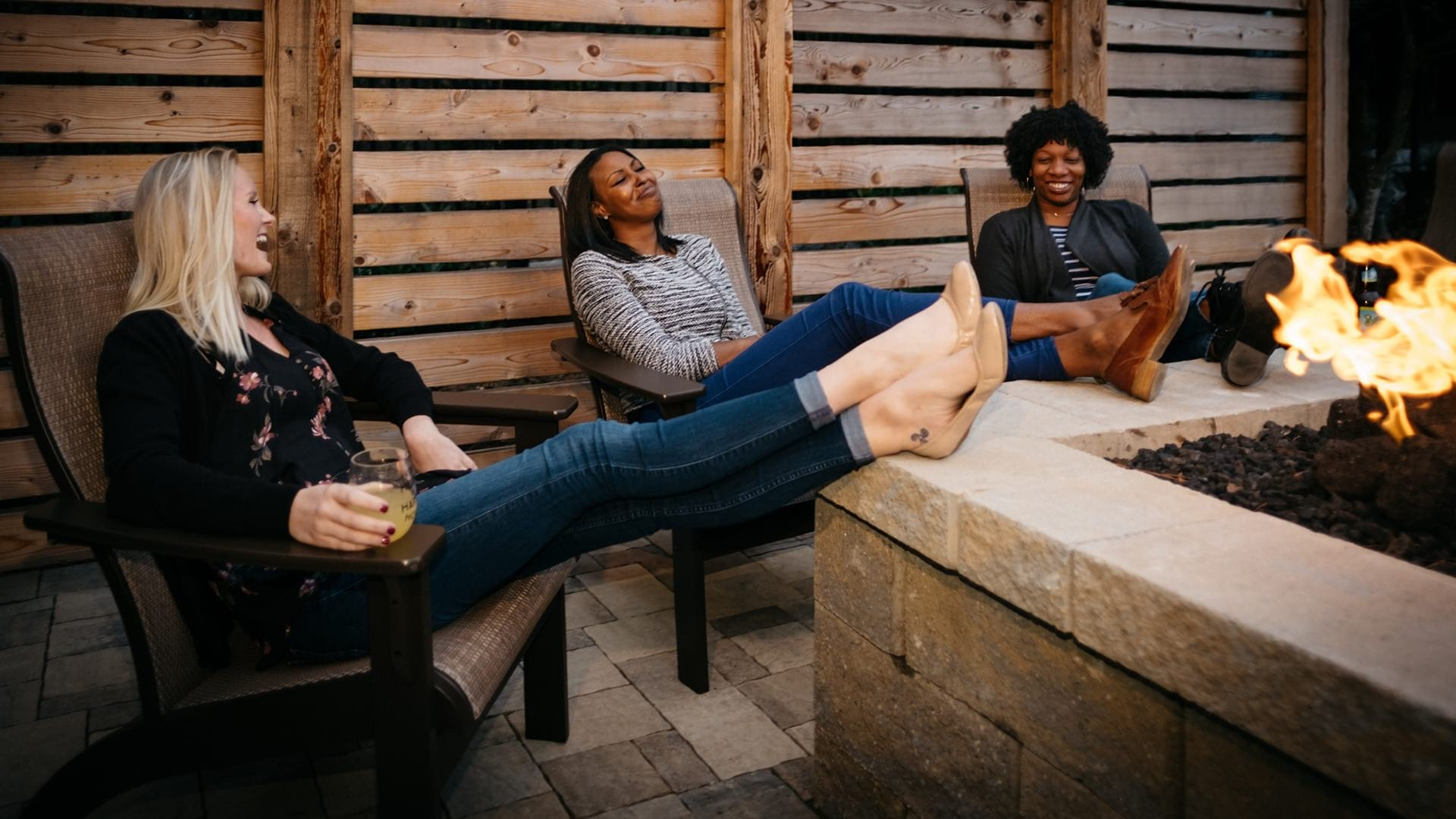 three women laughing and talking around the fire pit