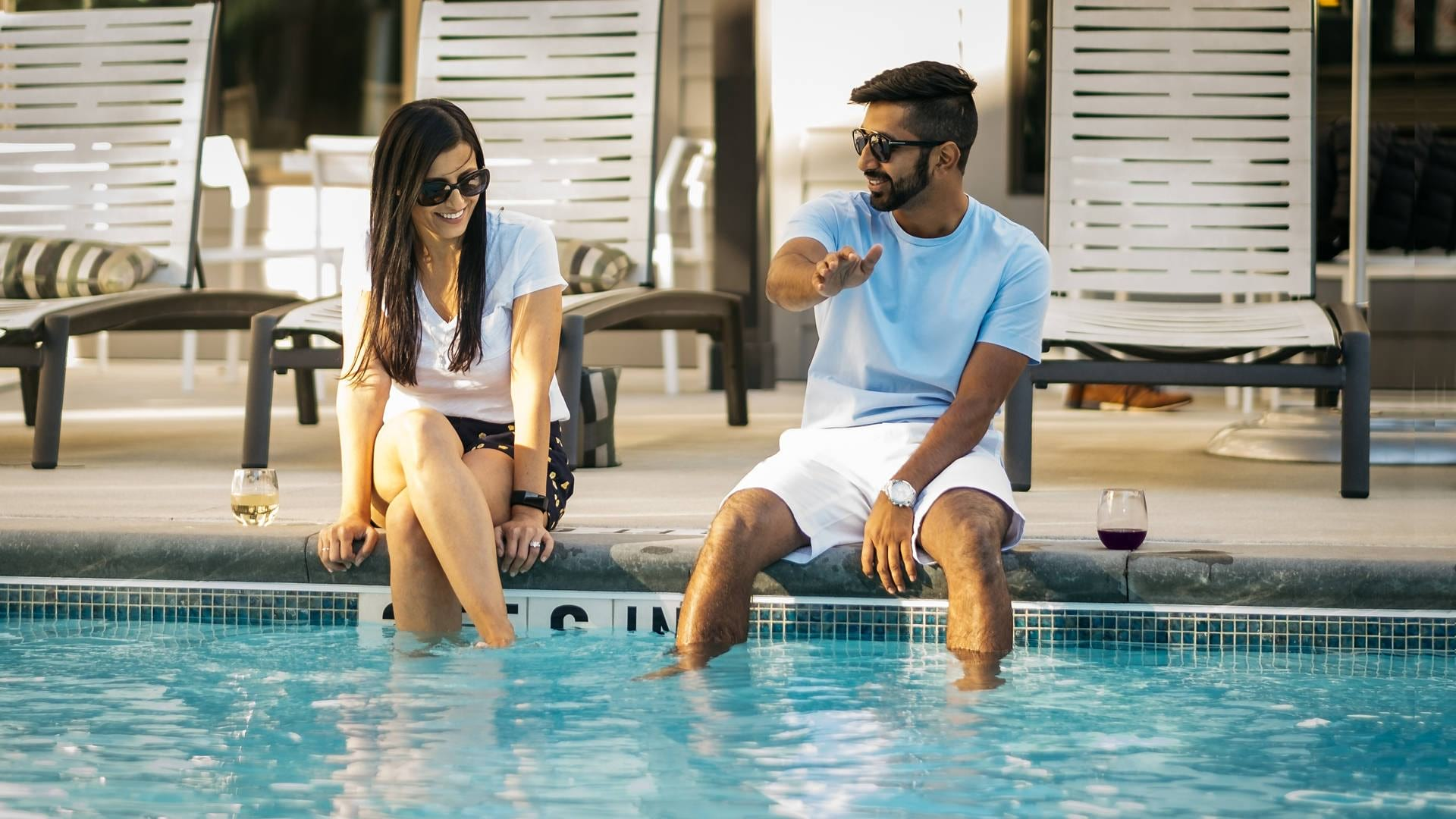 couple sits on pool ledge, wading their legs and talking
