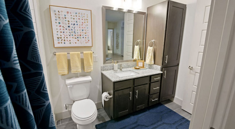 Spacious bathroom with modern lighting and granite countertops at our CityLine apartments in Richardson