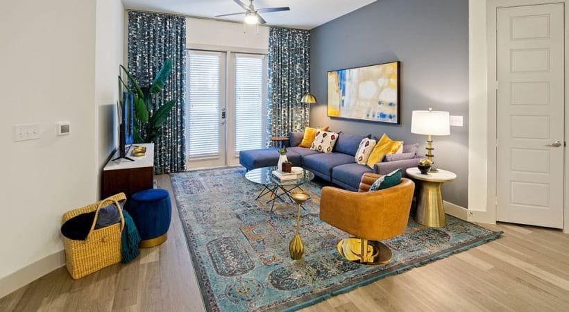 Living room with accent wall and wood-style flooring at our spacious apartments in North Dallas, TX