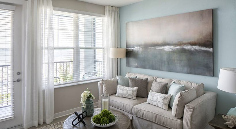 Cozy living room with light blue accent wall at our Bayside apartments for rent