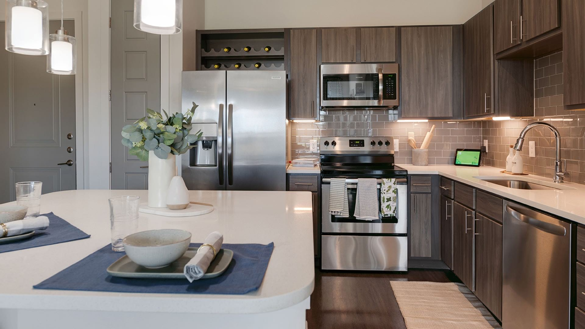 kitchen with pendant lighting over island and under cabinet lights to brighten countertops