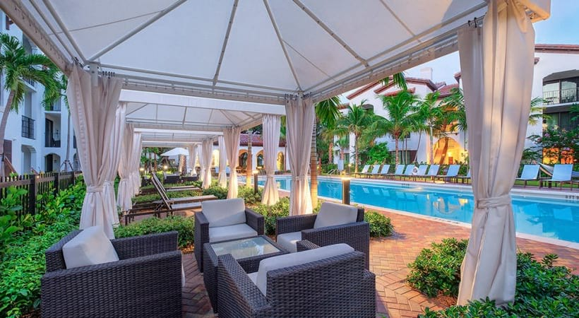 poolside cabanas with patio furniture and curtains to enclose for privacy
