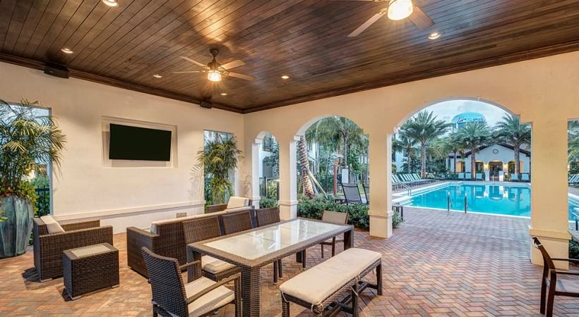 furnished outdoor lounge with mounted tv, ceiling fans and lighting fixtures