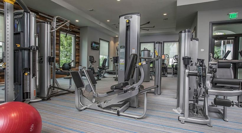 roomy fitness center with recessed lighting and large windows all around
