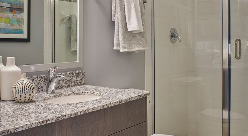 bathroom with walk-in, glass enclosed shower and ample lighting