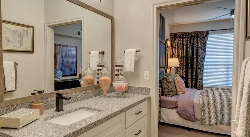 Well-lit bathroom with granite countertops