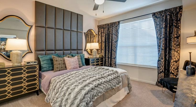 Spacious bedroom with large windows for light and ceiling fan