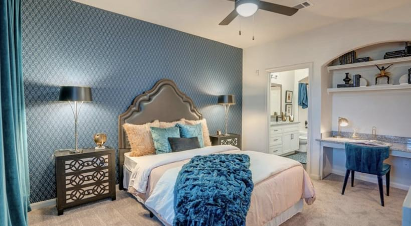 Spacious bedroom with a built-in desk and a ceiling fan
