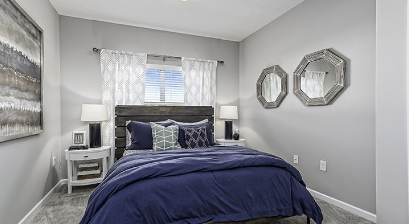 carpeted bedroom with light fixture above bed