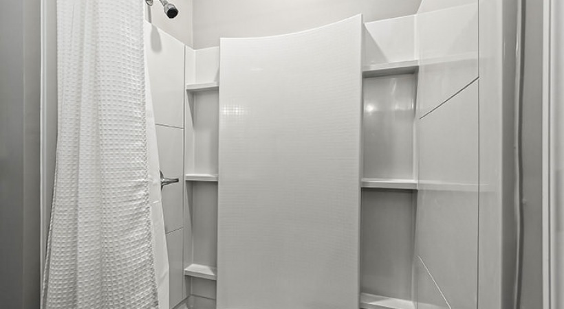 large shower with built-in shelves and overhead lighting