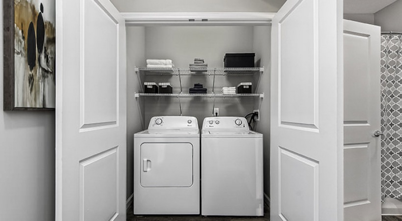 brightly lit laundry closet with shelving and side-by-side washer/dryer