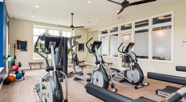 brightly lit fitness center with large windows