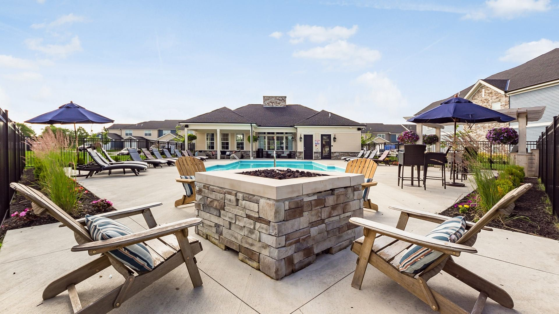 outdoor fire pit with lounge chairs next to pool