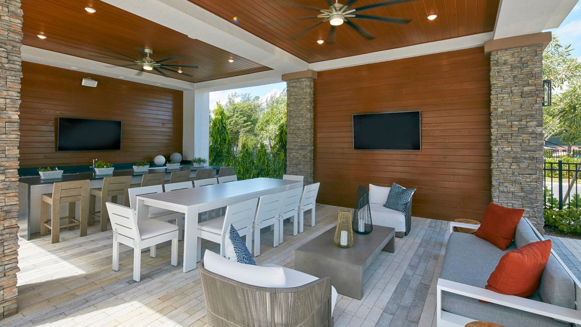 outdoor lounge with kitchen, dining areas and tvs