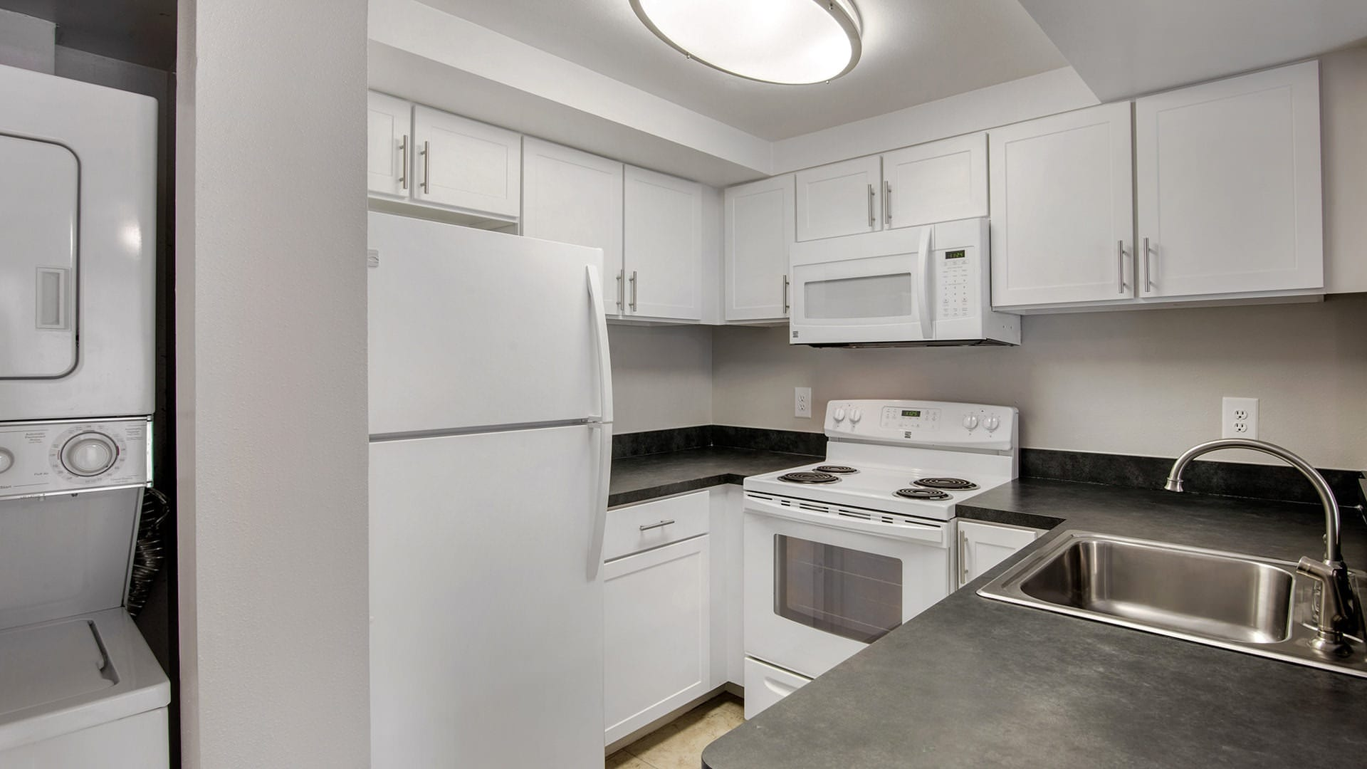 lighted kitchen next to stacked washer/dryer