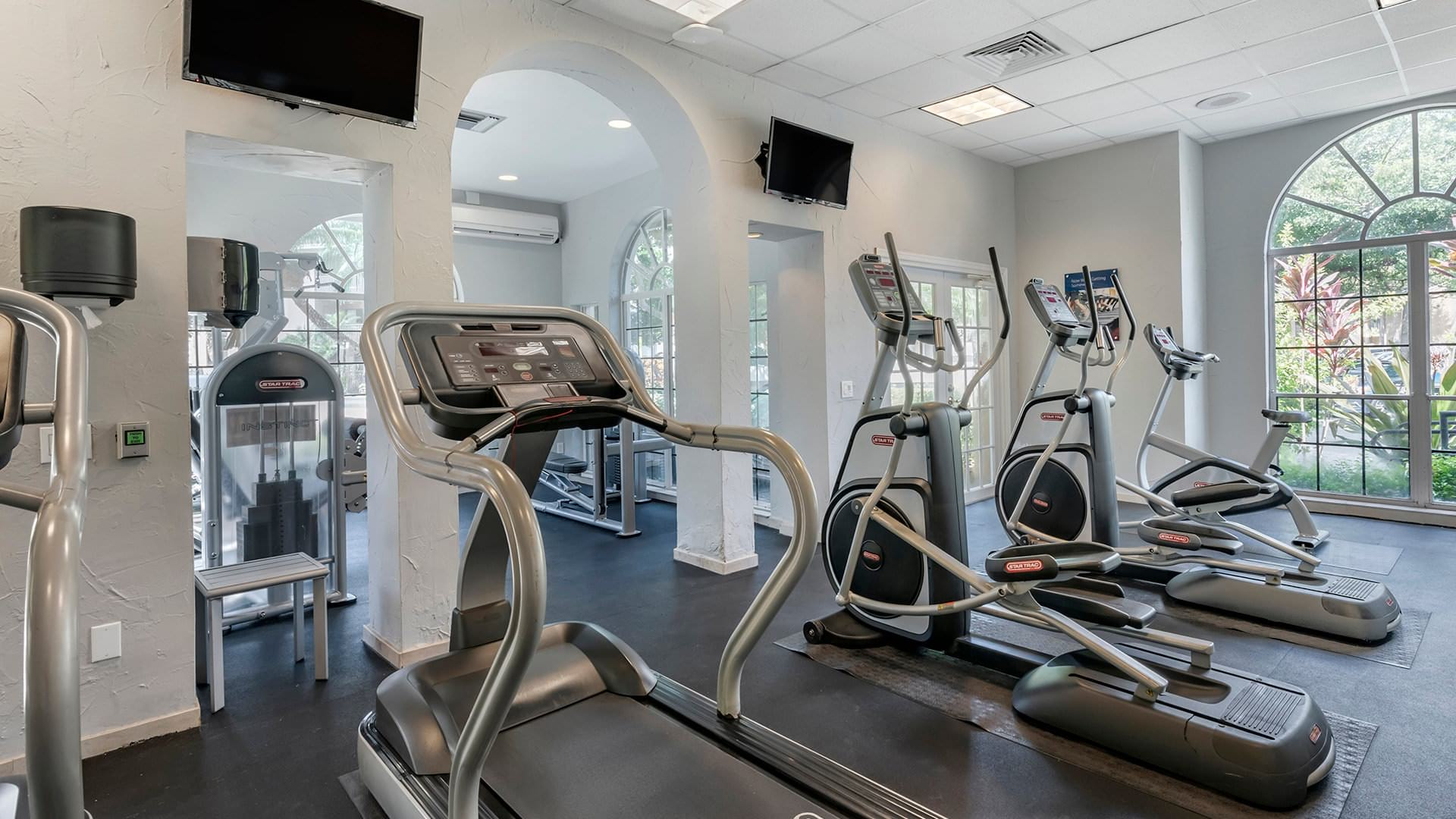 cardio machines in brightly lit fitness center