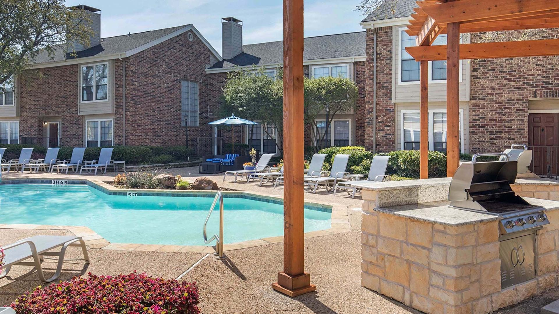 Spacious pool with a large pool deck and outdoor grill