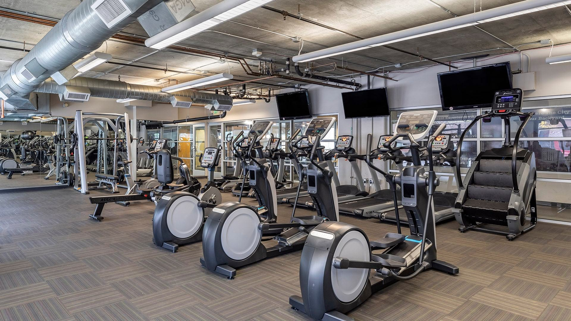 cardio machines face mounted tvs in well lit fitness center