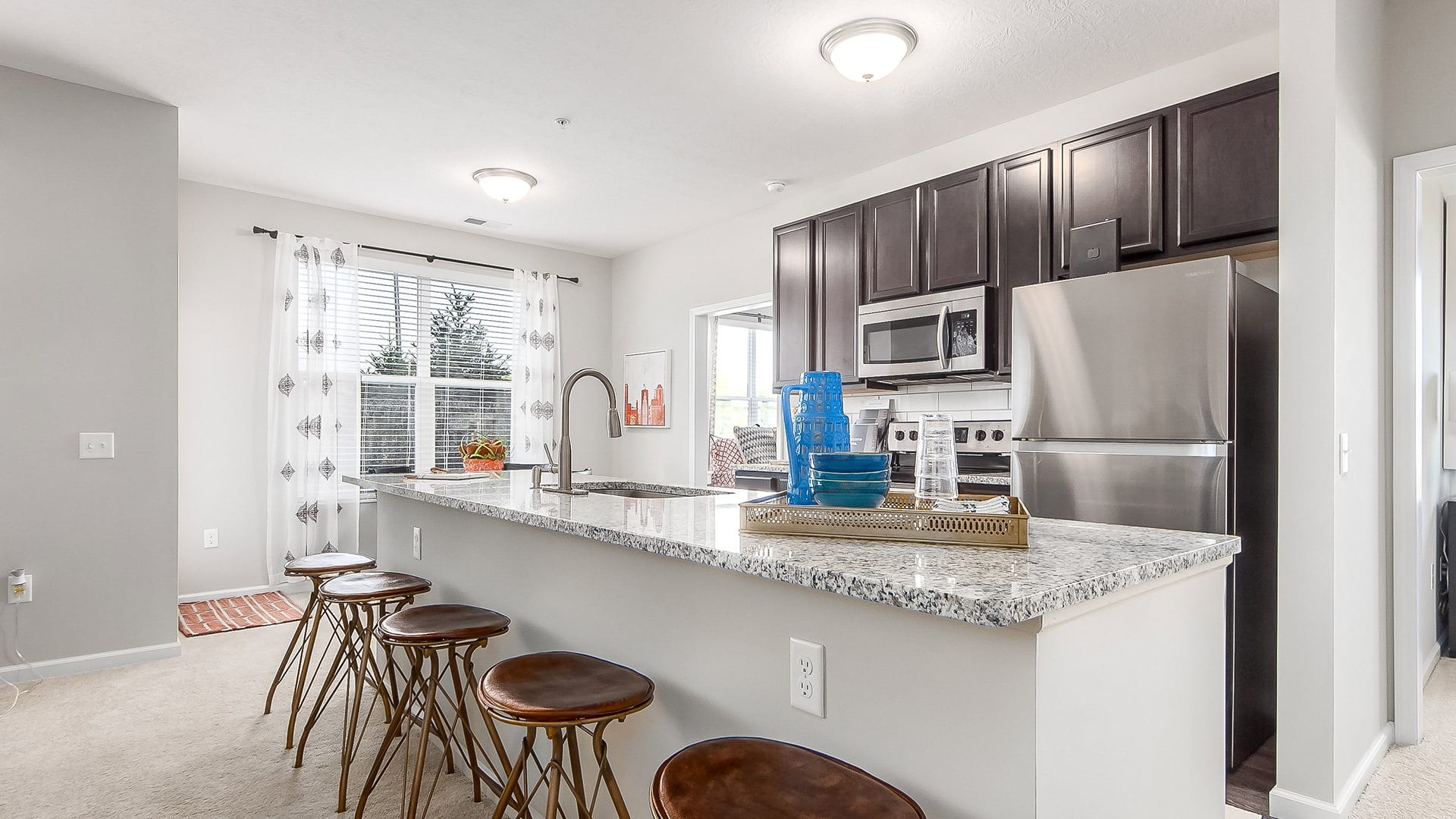 Spacious and well lit kitchen with tiles floors and stainless steel appliances