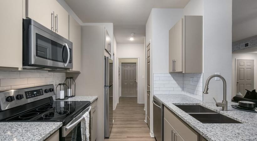 Kitchen with designer tile backsplash at our luxury apartments near Richardson, TX