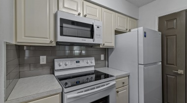 Apartment kitchen with white appliances