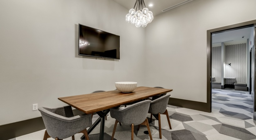 Conference room with a spacious table, modern seatings, and HDTV at our luxury apartments in Frisco, TX.