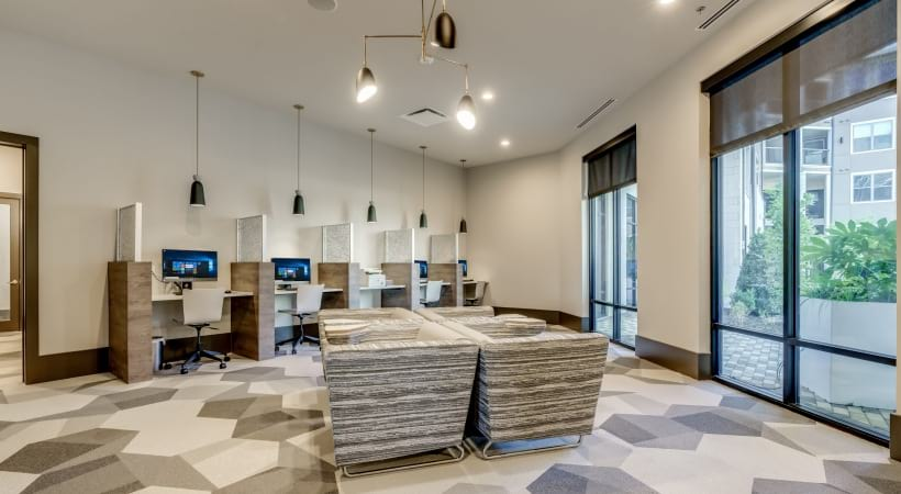 Business center with multiple computers and seatings at Circa apartments in Frisco, TX