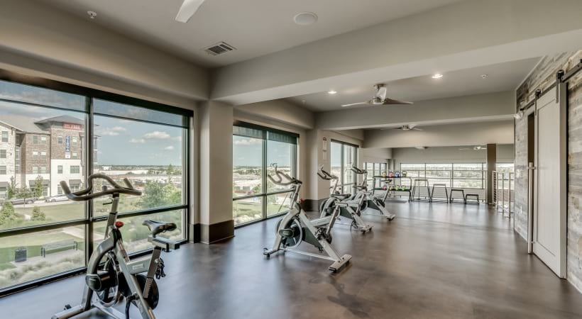 Our spacious spin studio with stationary bikes and big windows looking out to Circa Verus Frisco apartment courtyard